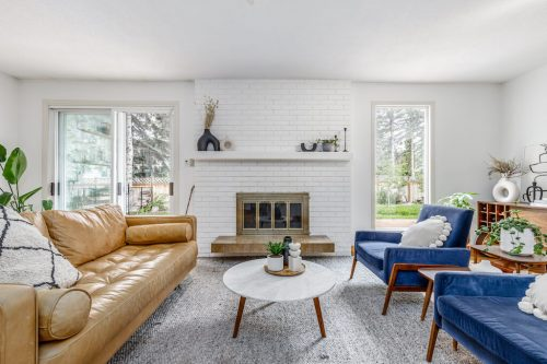 Mid century modern design and style in living room with white brick fireplace at 6911 Lowes Court SW in Calgary Alberta